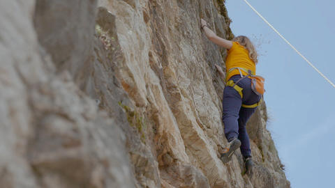 A female rock climber climbs up a rock. Learning to climb Live Action