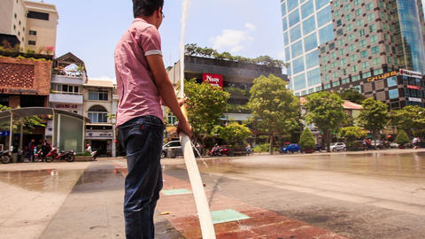 Vietnamese Guy Washes Central Square with Hose in Ho Chi Minh Footage