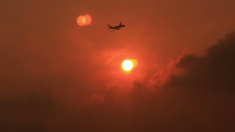 Airliner Flies above Clouds against Sun Disk at Sunset Footage