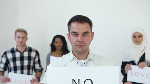 """Serious young handsome man holding in his hands poster with words """"No racism"""" on Live Action"""