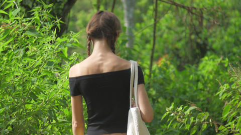 lady walks along green forestry landscape on sunny day Live Action