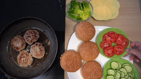 Frying meatballs in a pan and burger ingredients. Vegetables bun and cheese Live Action