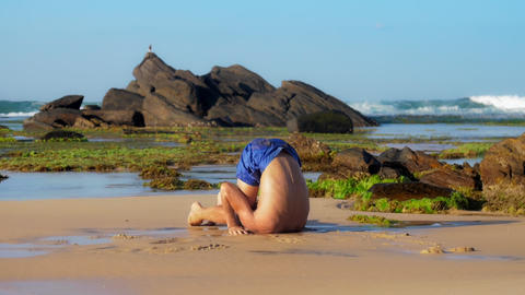 muscular sportsman meditates in yoga pose on wet sand Live Action