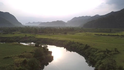 bright sun reflecting in calm river against peanut fields Live Action