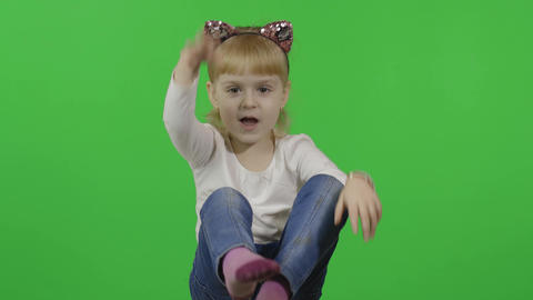 Girl in jeans and headband with a cat ears. Happy four years old child. Chroma Live Action