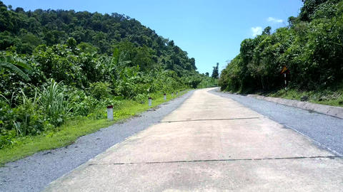 winding jungle road with black white poles and gray barriers Live Action