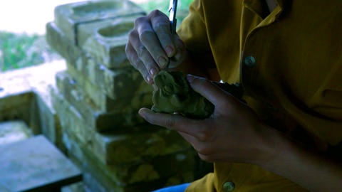 close view woman makes traditional orient dragon with clay Live Action