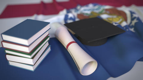 Graduation cap, books and diploma on the flag of Missouri. Higher education in Live Action