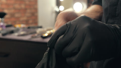 Male hands wearing black latex gloves in beauty salon. Hands on hair stylist in Live Action