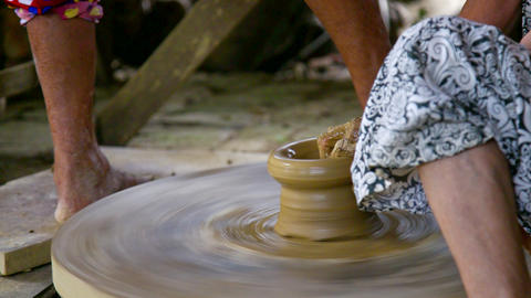 assistant rotates wheel by bare foot potter models vase Live影片