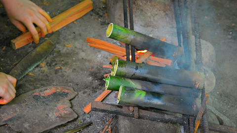 Asian Artisan Drying Bamboo Tubes over a Fire Live Action
