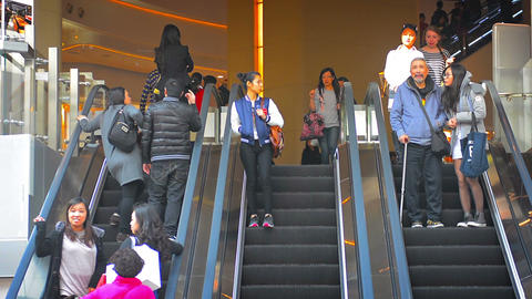 Crowds of pedestrians ascending and descending a triple wide bank of escalators Footage