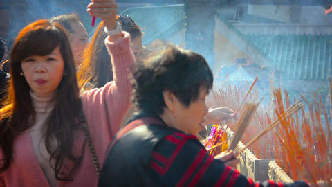 Buddhist worshippers leaving smoldering incense sticks at an alter at Wong Tai S Footage