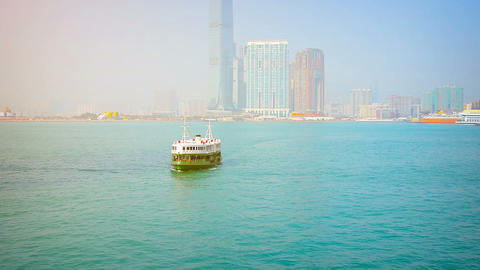 Green and white passenger ferry approaching the pier with the Hong Kong skyline Footage
