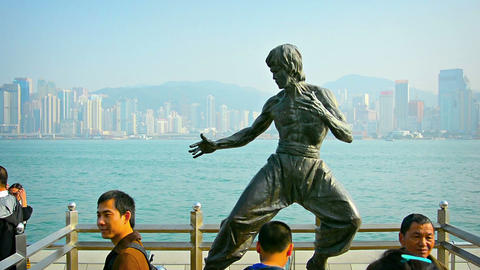 Tourists posing for photos and selfies in front of a bronze statue of Bruce Lee Footage