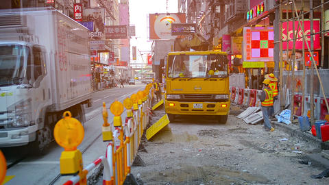 Crane equipped truck backing up under direction of laborers at an urban construc Footage