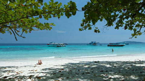 Tourists basking in the sun as gentle Waves wash a Beautiful. Tropical Beach on Footage