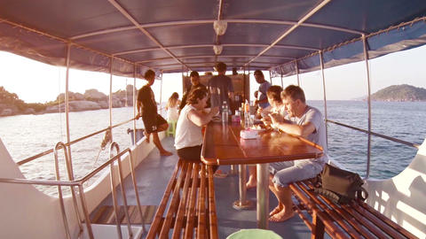 Tourists enjoy a delicious meal on their tour boat as they travel to Thailand's Footage