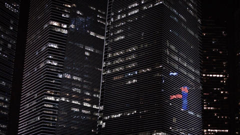 Panning shot of big. contemporary. angular. highrise office buildings at night.  Footage