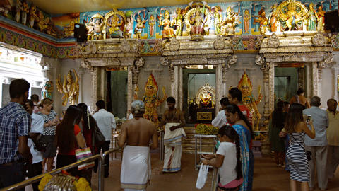 Hindu worshippers come to pray and give offerings inside a temple in the Indian Footage