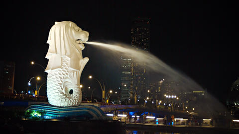 The dramatically lighted Merlion fountain. with a continuous spray of water into Live Action