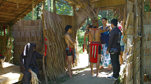 Local tribal chief in traditional clothes. greets tourists at the entrance to hi Footage