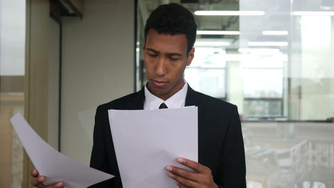 Black Businessman Reading Documents in Office Footage