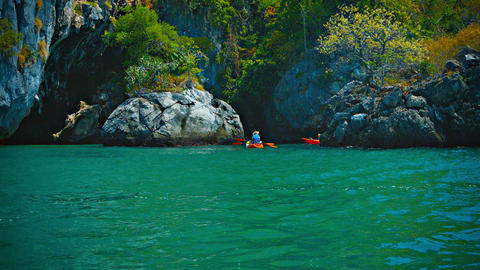 Kayakers Exploring a Rocky Inlet along a Tropical Coastline Footage