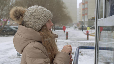 Teenager girl choosing goods in street kiosk on winter walk. Smiling girl buyer Live Action