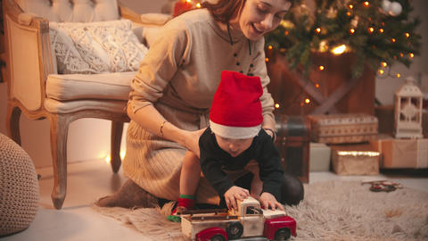 A young smiling woman playing with her little baby wearing a red hat - playing Live Action
