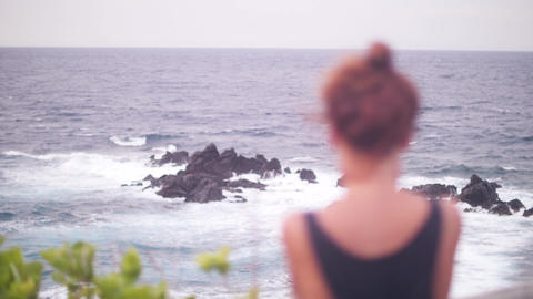 Young woman with red hair enjoying the view of the ocean and distant horizon Live Action