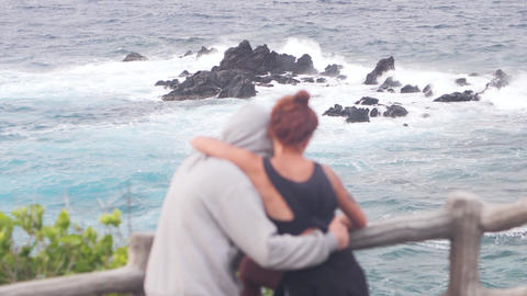 Back view of a couple hugging each other and enjoying the view of the sea Live Action