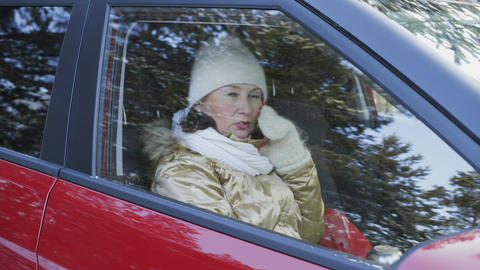 Attractive woman in hat and winter jacket talking by mobile phone in car Live Action