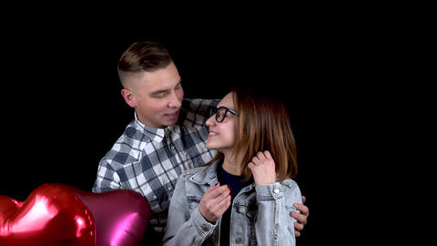 A young man gives a young woman heart-shaped balloons. The woman closed her eyes Live Action