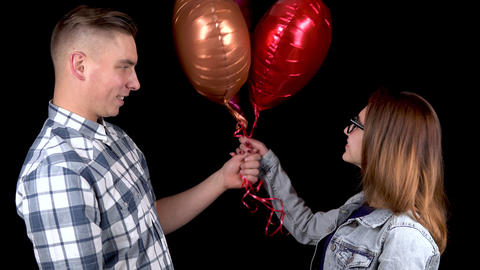 A young man gives a young woman heart-shaped balloons. Man and woman kissed on a Live Action