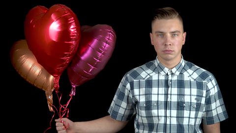 Sad young man let go of heart-shaped balloons. A sad man stands with helium Live Action