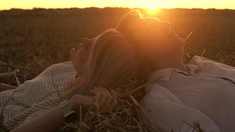 Loving man and woman are laying on the grass head to head Live Action