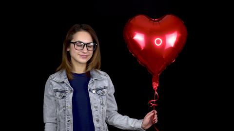 A young woman kisses an inflatable balloon in the form of a heart. Woman with a Live Action