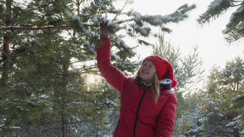 Young woman in red clothes and hat walking in snowy forest at Christmas vacation Live Action