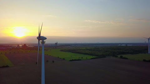 Aerial footage of a wind turbine in front of the setting sun Wind Power - Live Action