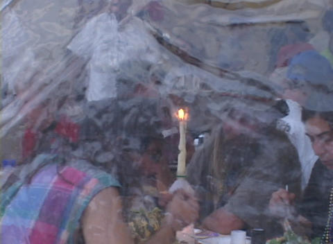 Zoom out from a group of refugees eating dinner in a FEMA tent Footage