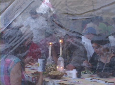 Zoom out from a group of refugees eating dinner in a FEMA... Stock Video Footage