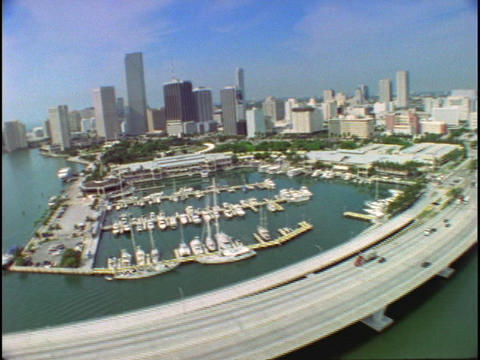 Watercraft dock in a marina and vehicles travel a roadway in Miami, FL Live Action