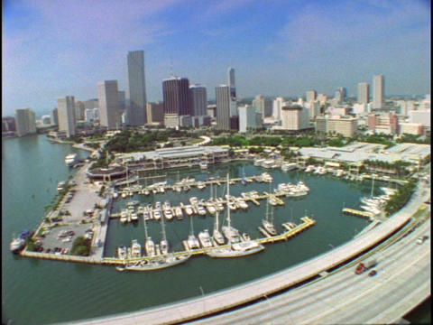 Watercraft dock in a marina and vehicles travel a roadway... Stock Video Footage