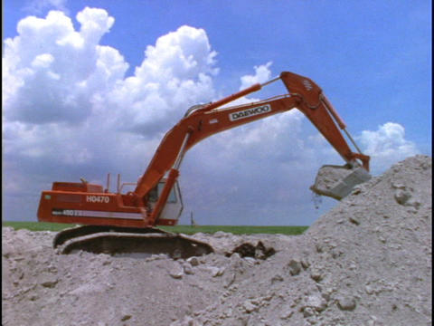 A steam shovel piles dirt at a construction site Live Action