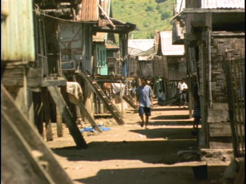 A villager walks between huts in Sulawesi, Indonesia Stock Video Footage