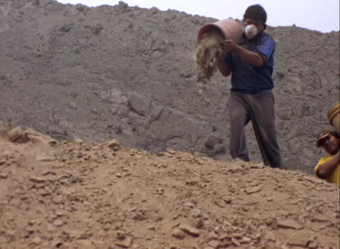 Medium-shot of two men dumping buckets of dirt at an... Stock Video Footage