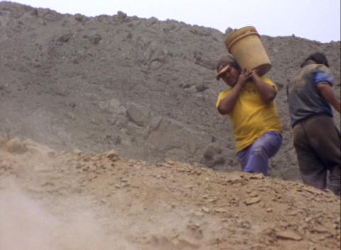 Medium-shot of two men dumping buckets of dirt at an archeological site Footage