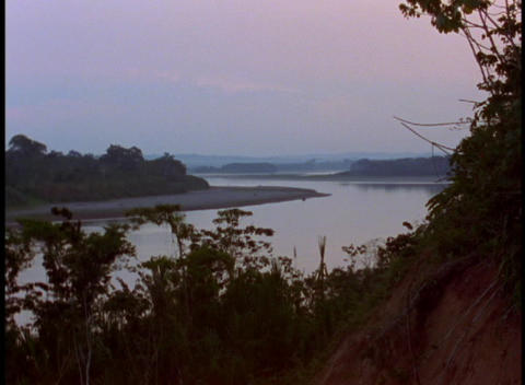 Medium shot of a river flowing through the jungle in the Amazon rainforest Footage