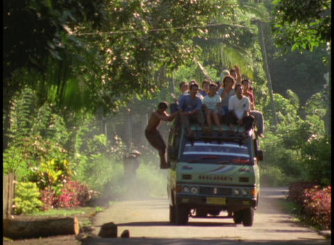 Natives ride on the top of a crowded mini bus down a... Stock Video Footage